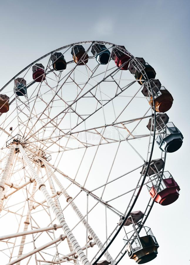 Vertical low angle shot of a tall Ferris wheel with the beautiful clear sky in the background. A vertical low angle shot of a tall Ferris wheel with the royalty free stock photos