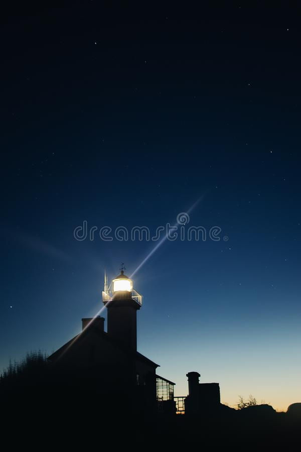 Vertical low angle silhouette shot of a lighted tower under a starry sky. A vertical low angle silhouette shot of a lighted tower under a starry sky royalty free stock image