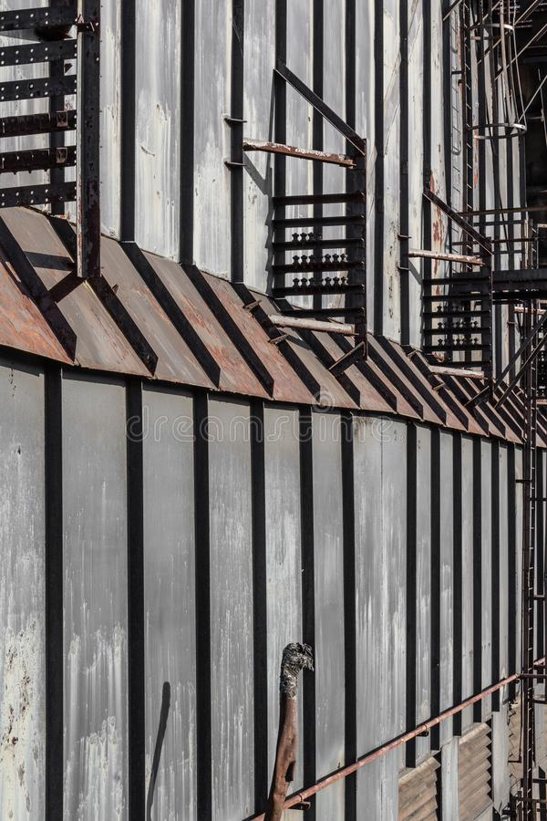 Vertical metal panels against a tall wall, perspective view stock images