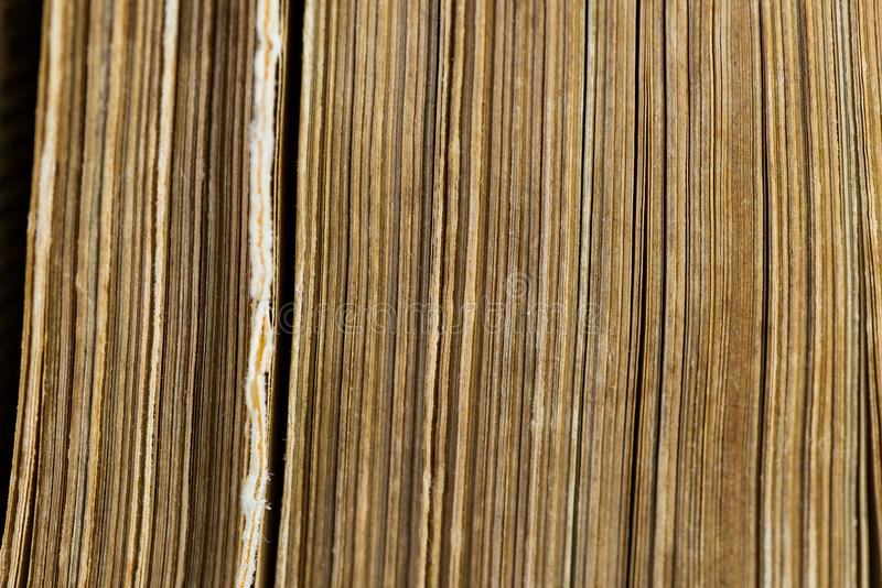 Vertical old aged yellow book pages close up macro shot. Image for background stock photos
