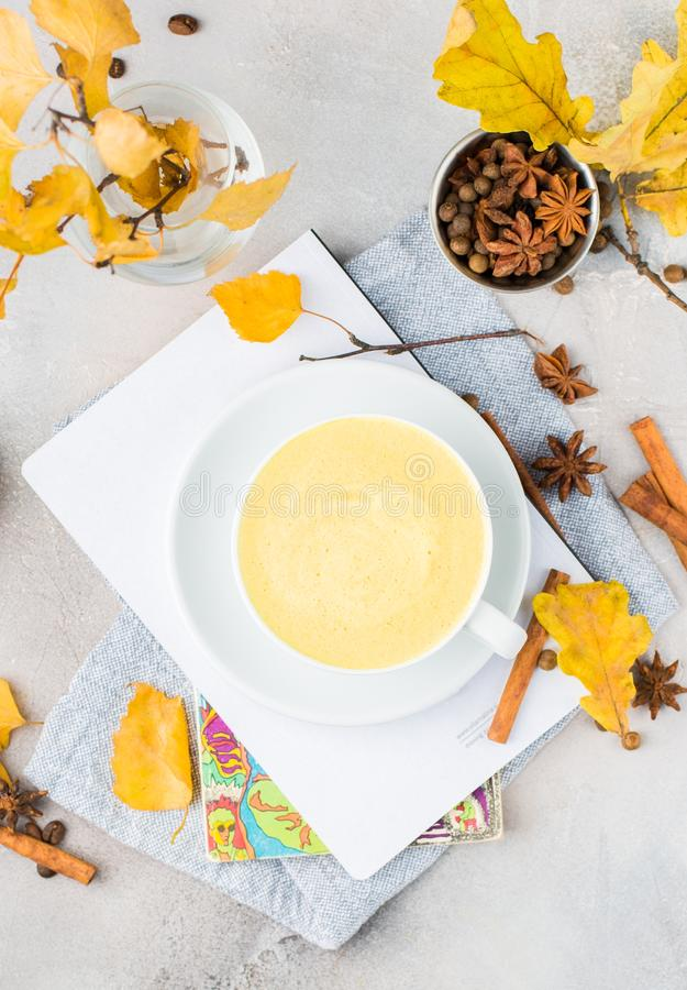 Vertical overhead shot of milk coffee in a white ceramic cup on a table decorated in fall colors. A vertical overhead shot of milk coffee in a white ceramic cup stock photo