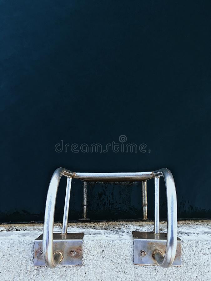 Vertical overhead shot of a silver ladder in a pool. A vertical overhead shot of a silver ladder in a pool royalty free stock photos