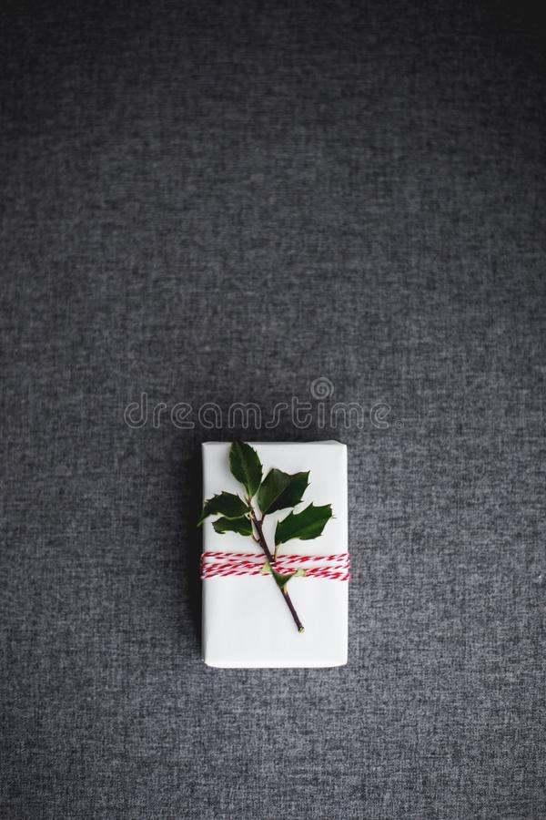 Vertical overhead shot of a white Christmas gift box decorated with a small branch with green leaves. A vertical overhead shot of a white Christmas gift box royalty free stock images