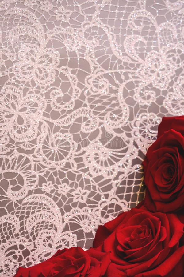 Beautiful red roses in white floral lace background. Valentine`s Day or romantic celebration concept, with copy space. Vertical photo of beautiful red roses in royalty free stock photos