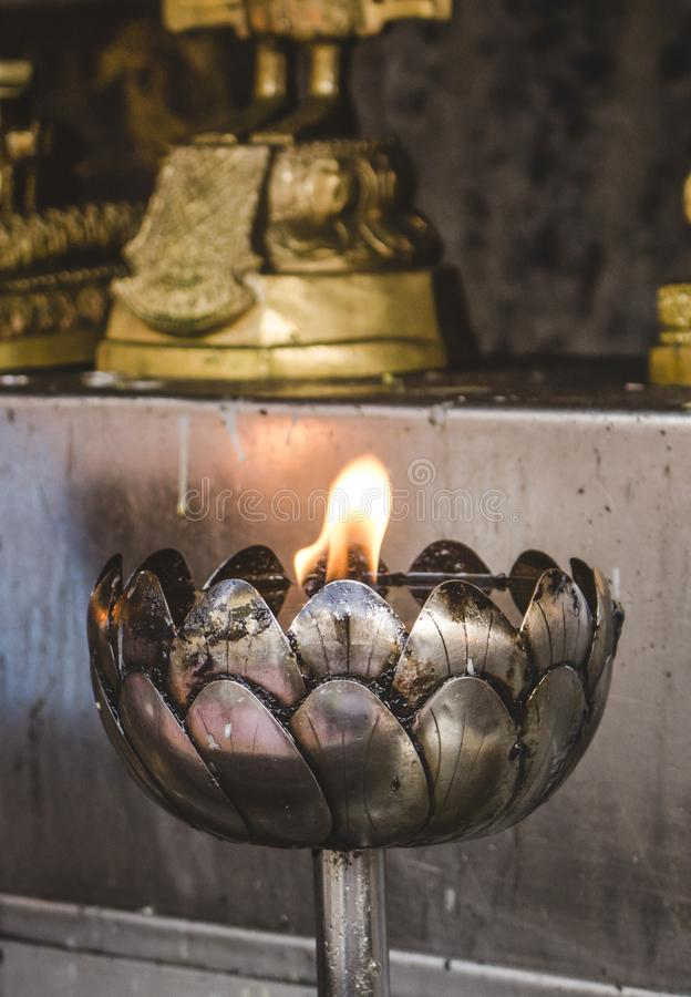 Beautiful Thai style metal oil lantern burning in Buddhist temple in Thailand. With copy space. stock photography