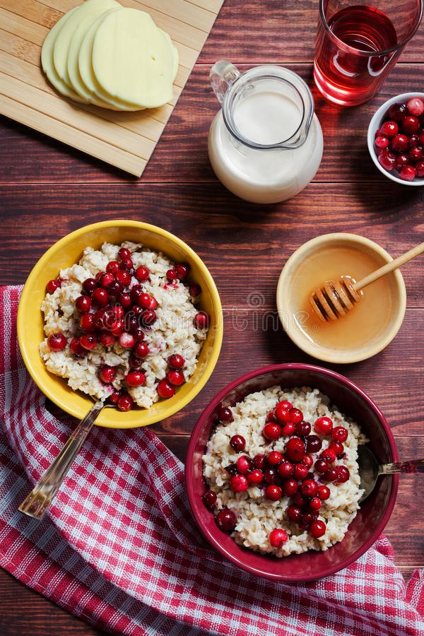 Oat porridge with cranberries. A vertical photo of bowls of oat porridge with cranberries royalty free stock image