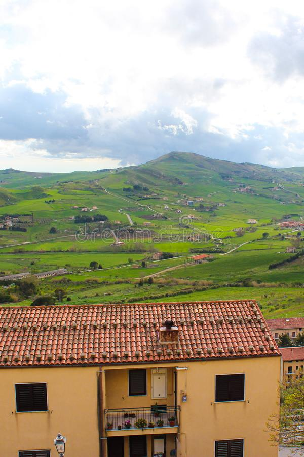 Vertical photo capturing amazing Sicilian landscape with houses in village Gangi in Italy. Cloudy day. Green hilly countryside. Popular tourist destination royalty free stock photos