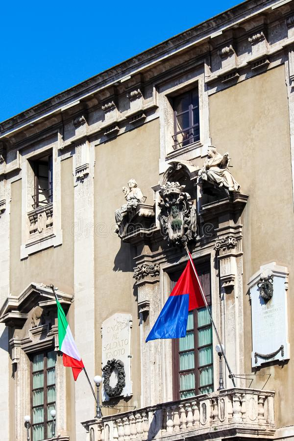 Vertical photo capturing front side facade of historical Town Hall in Catania, Sicily, Italy. On the balcony there are waving royalty free stock photos