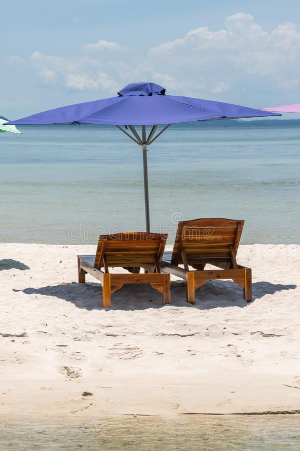 Vertical photo of chair and umbrella on the white sand beach. Vertical photo of lounge chair and umbrella on the white sand beach stock photos