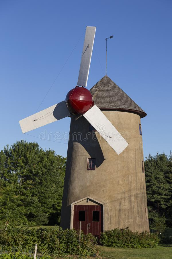 Concrete windmill with cedar shingled roof, red and white sails and dark red door stock photo