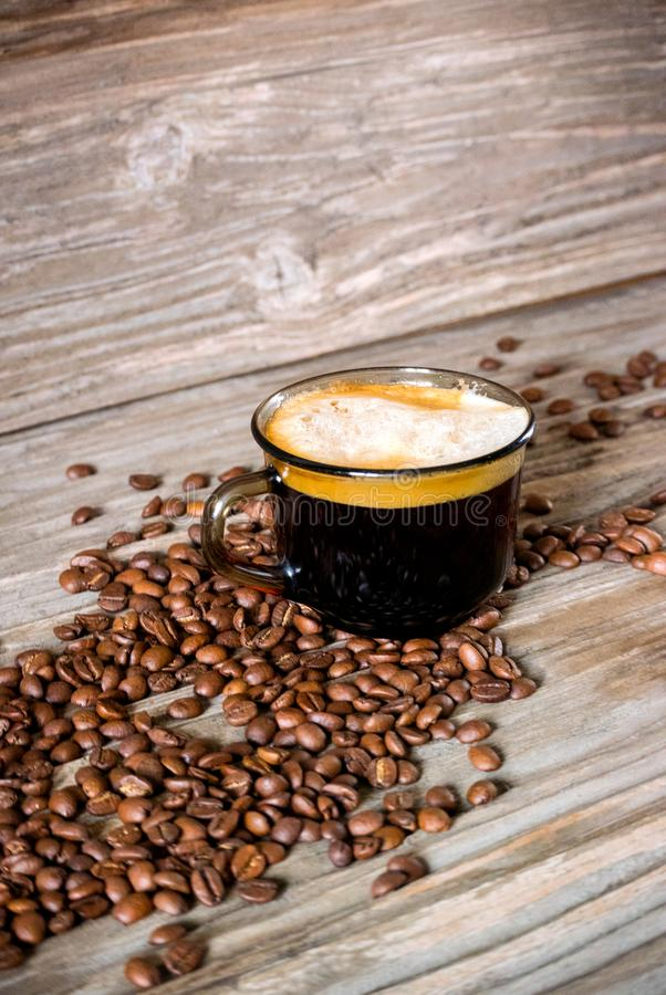 Vertical photo of a cup of fragrant black coffee on a background of coffee beans and a wooden table royalty free stock photo