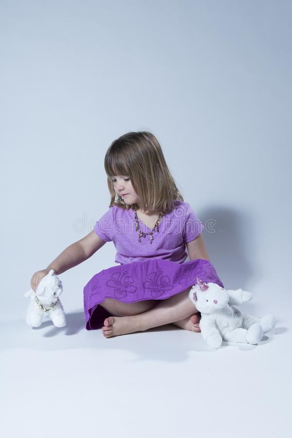 Vertical photo of cute little girl in mauve top and purple skirt sitting cross-legged royalty free stock photo