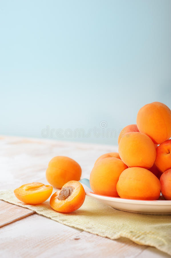 Vertical photo of Delicious ripe orange apricots in a bright plate on wooden table with green napkin on light blue wall background. Fresh juicy fruits. Bio royalty free stock photos