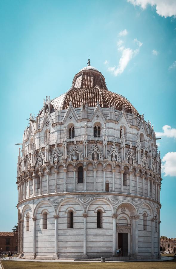 Vertical photo with famous babtistry Battistero di San Giovanni in Pisa. Building is on square Piazza dei Miracoli with leaning. Tower. Sky is light blue with stock image