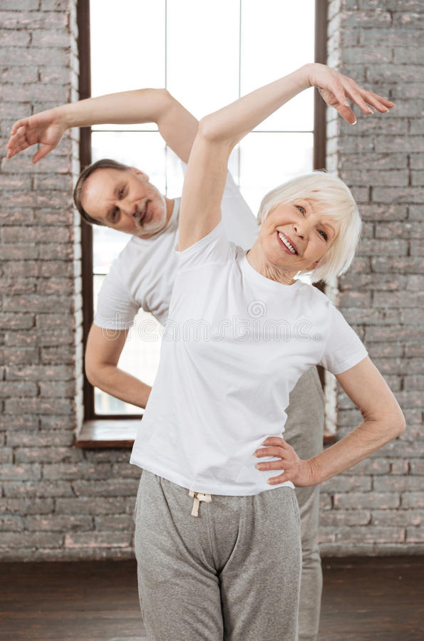 Vertical photo of happy couple while doing sport. Good shape. Positive delighted people wearing white T-shirts holding hands on the waist while keeping smile on stock images