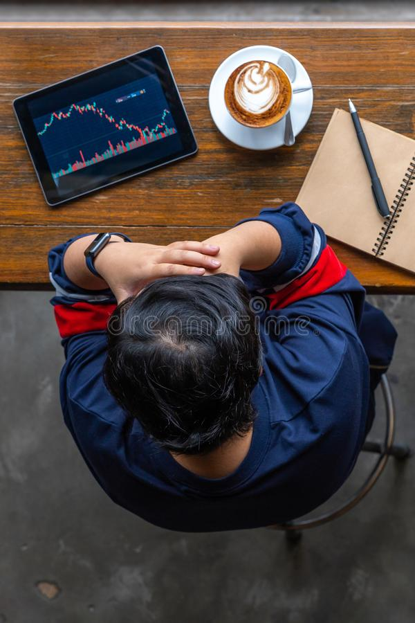 Young Asian investor having headache while watching stock trading graph. Vertical photo of investor having headache while watching stock trading graph royalty free stock image
