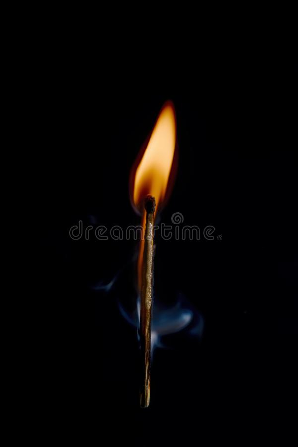 Safety match on black background with flaming head. Vertical photo of match stick. The safety match has flaming hot head but the body is still fine. Nice curly royalty free stock photo