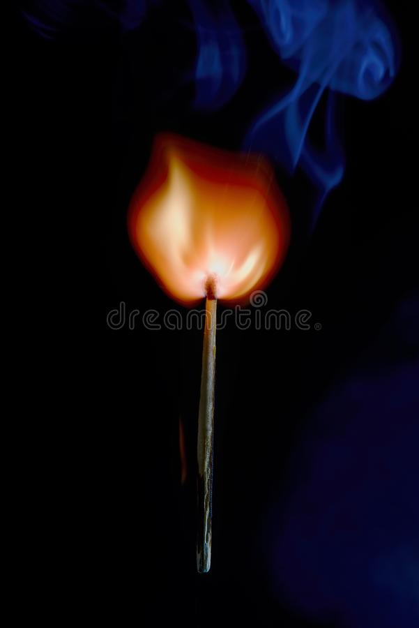 Safety match on black background with flaming head. Vertical photo of match stick. The safety match has flaming hot head but the body is still fine. Nice curly stock photos