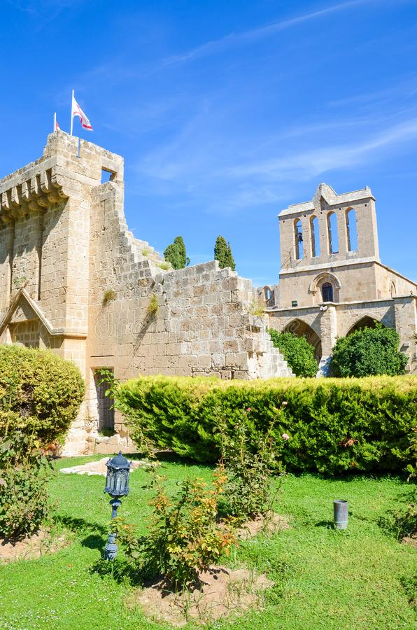 Vertical photo of medieval Bellapais Abbey in Turkish Northern Cyprus. Captured with the adjacent park and with blue sky. Significant historical site and royalty free stock photography