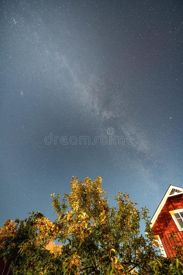 Vertical photo milky way stars at blue sky above red swedish wooden house and apple tree in the garden at end of summer, autumn. Vertical photo of Milky Way stock images