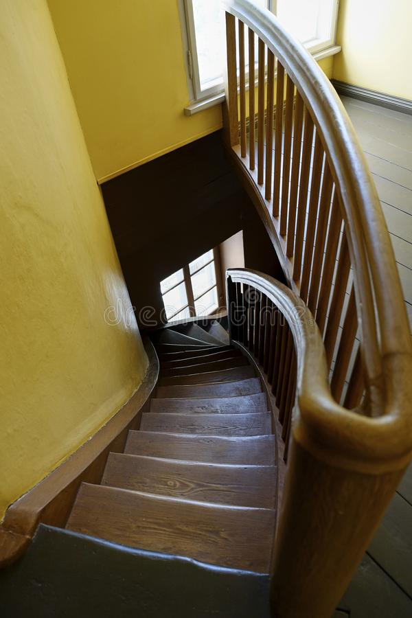 Vertical photo Old wooden round staircase spiraling stock photo