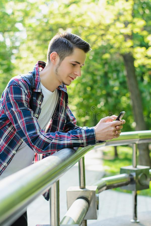 Vertical photo portrait of cheerful nice handsome positive glad person leaning on railing sending notification to girlfriend royalty free stock image