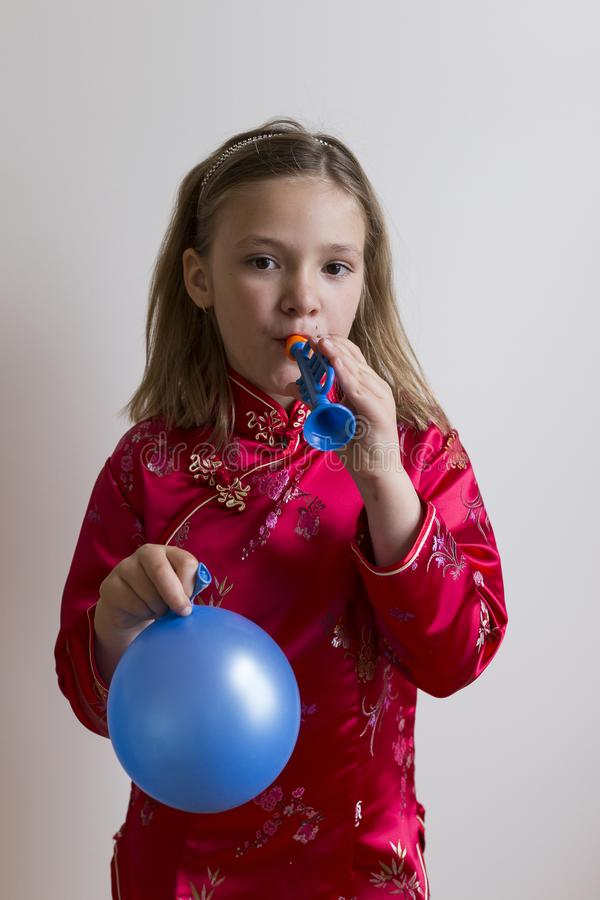 Pretty young girl in red blowing in a toy trumpet royalty free stock photos
