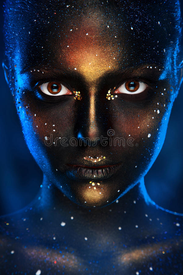 Vertical photo of pretty woman with black face art. In studio stock photo