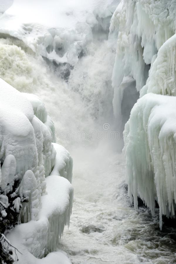 Vertical photo of small waterfalls cascading into narrow river with banks covered in snow and icicle royalty free stock photo
