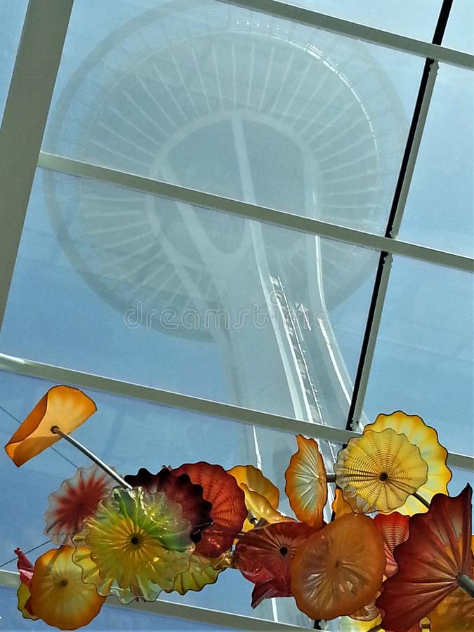 Vertical photo of Space Needle above Chihuly. Red, yellow and orange Chihuly glass flowers frame the Seattle Space Needle in the artist`s exhibit at the Needle`s stock images