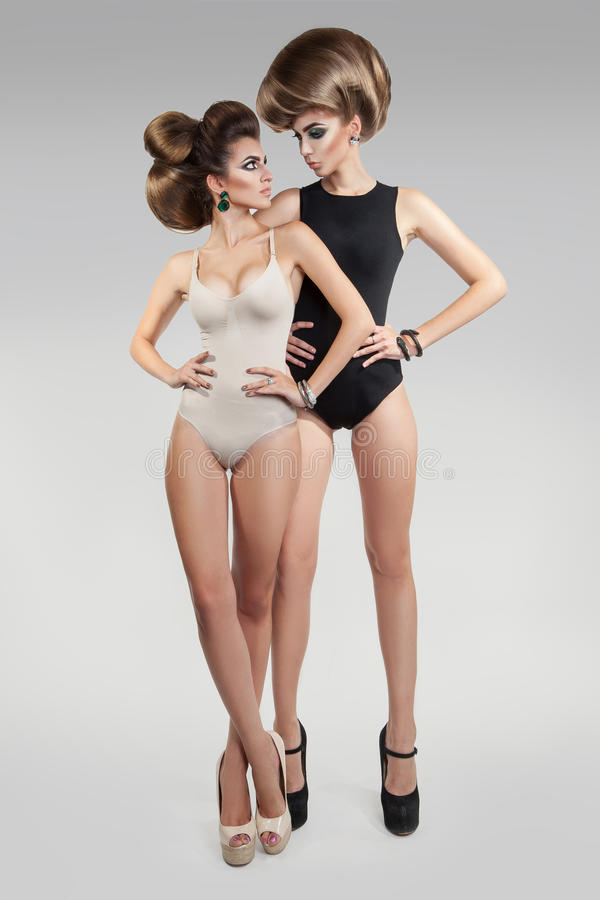 Vertical photo of two beauty women in studio with creative hairs stock images
