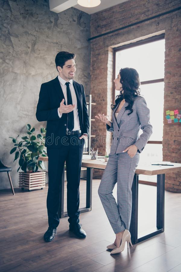 Vertical photo of two business people communicating standing workshop dressed formal wear suits stock image