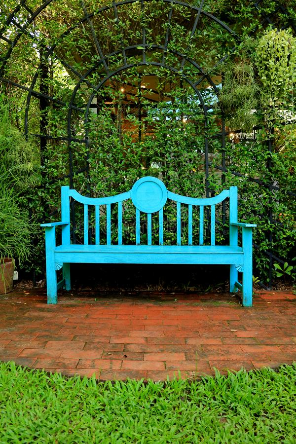 Vertical photo of a vivid blue colored wooden bench on terracotta brick pathway. In green garden royalty free stock photos