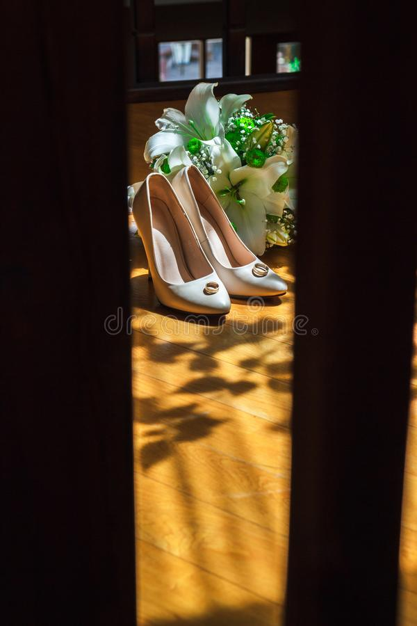 Vertical photo wedding bouquet, bridal shoes and wedding rings on light rays. Wedding shoes, partially illuminated by sunlight, partially in the shade stock photos