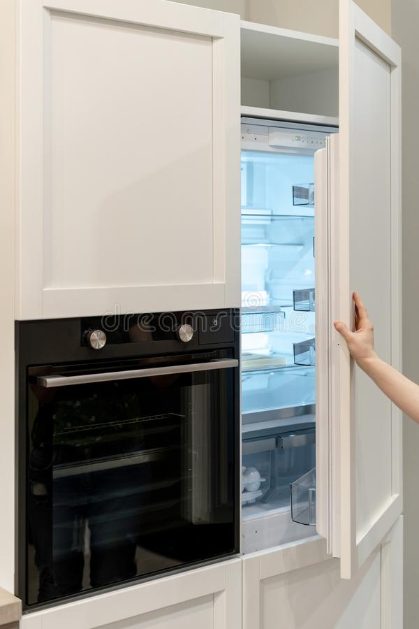 Woman hand opening white modern empty freezer. Vertical photo of woman hand opening white modern empty freezer built-in in kitchen cabinet with modern oven royalty free stock image