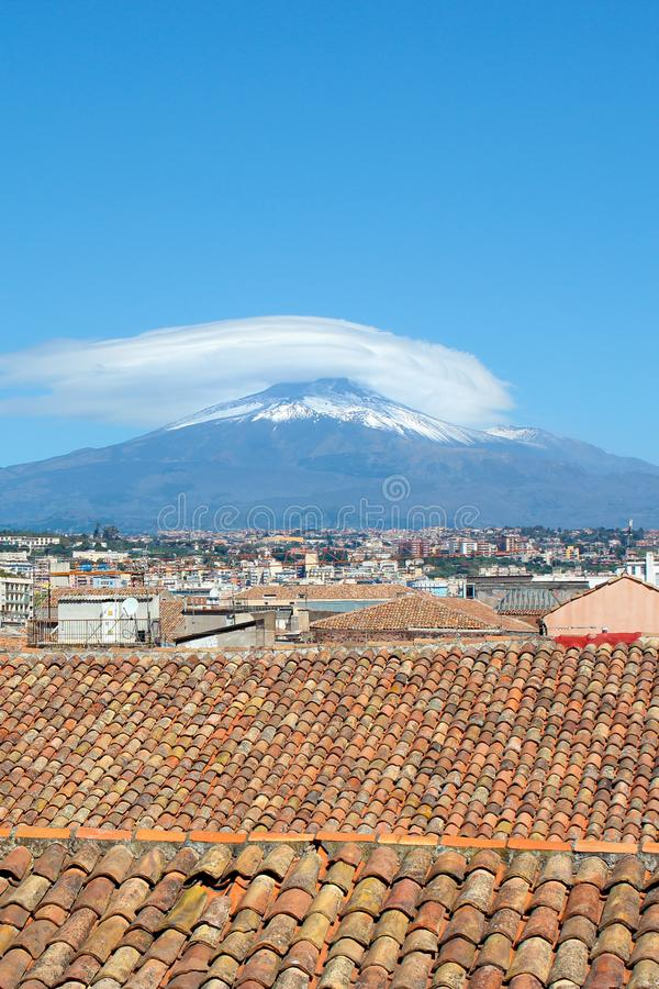 Vertical photography capturing beautiful cityscape of Catania, Sicily, Italy with famous Mount Etna volcano in background. Roofs of the historical buildings royalty free stock images