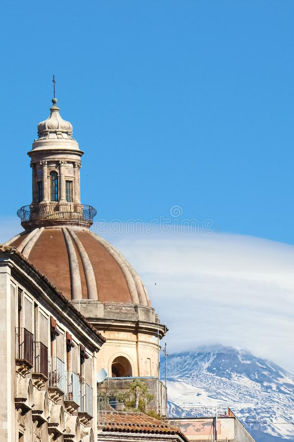 Vertical photography capturing the beautiful cupola of Roman Catholic Cathedral of Saint Agatha in Catania, Sicily, Italy. In background famous volcano Mount stock images
