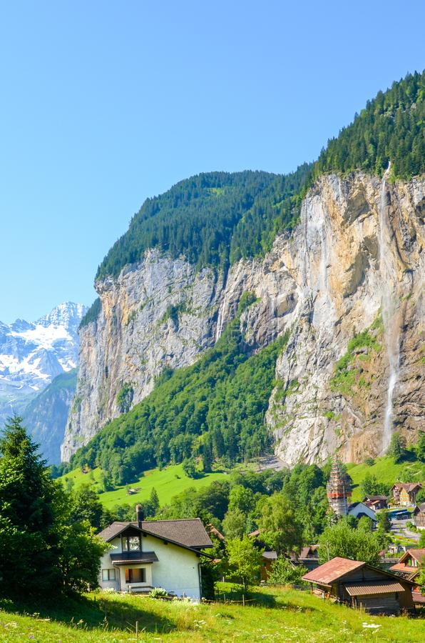 Vertical photography of picturesque village Lauterbrunnen in Swiss Alps. Famous Staubbach Falls in background. Tourists royalty free stock photography