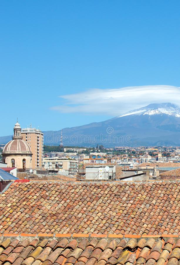 Vertical picture capturing beautiful cityscape of Catania, Sicily, Italy with dominant cupola of Cathedral of Saint Agatha. Majestic Mount Etna volcano in stock images