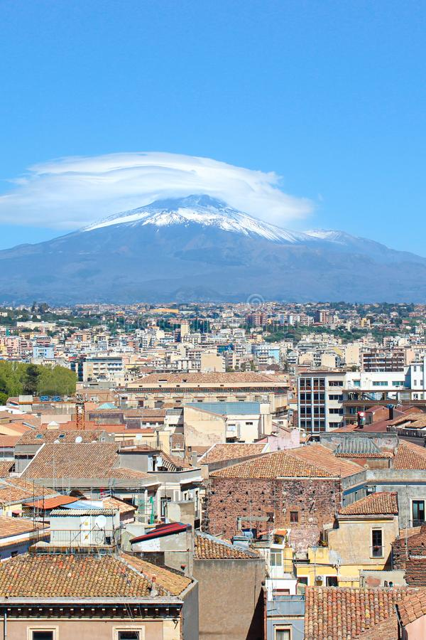 Vertical picture capturing famous Mount Etna overlooking the Sicilian city Catania, Italy. Smoke cloud over the famous volcano. Snow on the top. The beautiful royalty free stock photos