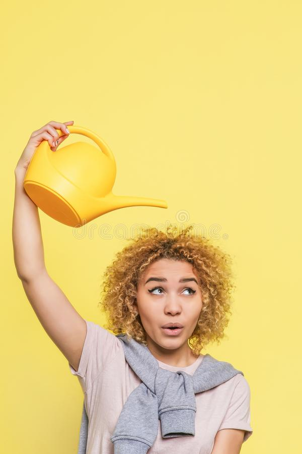 Vertical picture of funny girl. She holds a watering pot upon her hand. She is ready to pour some water on her hair stock photo