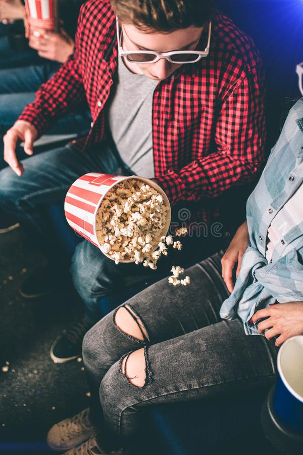 Vertical picture of guy looking at the basket of popcorn that is falling aside to the girl`s pants and legs. He is royalty free stock photography