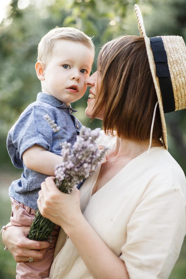 Vertical picture of mother holding her child on hands. Boy is looking straight royalty free stock photography