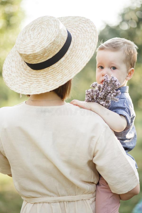 Vertical picture of mother holding her child on hands. Boy is looking straight and holding flowers royalty free stock photos