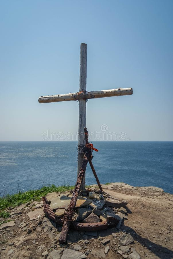 Vertical picture of old rusted anchor and wooden cross on the cliff break, sky and sea background, memorial royalty free stock photo