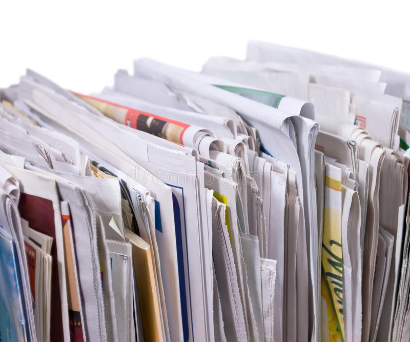 Vertical pile of newspapers and flyers. On white background stock photos