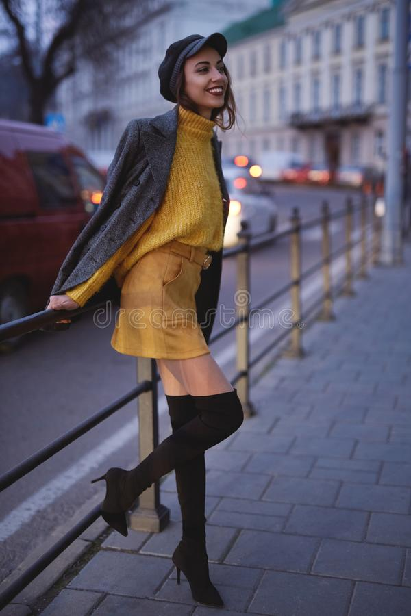 Beautiful fashionable woman in bright yellow sweater and skirt walking and posing outdoors. Vertical portrait of a beautiful fashionable stylish woman in bright royalty free stock photography