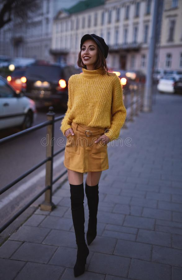 Beautiful fashionable woman in bright yellow sweater and skirt walking and posing outdoors royalty free stock photos