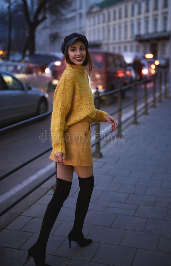 Beautiful fashionable woman in bright yellow sweater and skirt walking and posing outdoors. Vertical portrait of a beautiful fashionable stylish woman in bright royalty free stock image