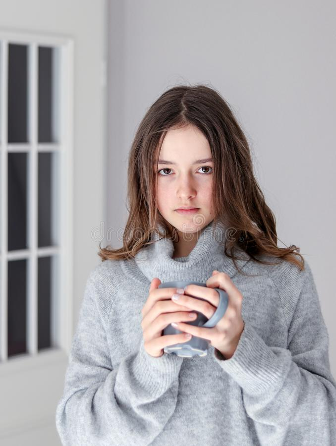 Vertical portrait of beautiful tween girl in warm grey pullover holding cup of tea looking at camera at home. Natural beauty without make up royalty free stock photos